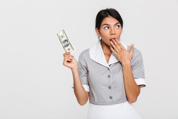 Ritratto della domestica attraente stupita in uniforme che tiene cento dollari mentre coprendosi la bocca di mano, guardando da parte Foto Gratuite