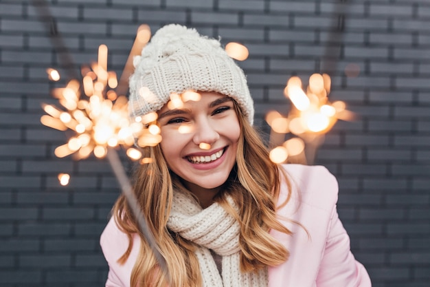 Portrait of amazing female model looking at bengal light with smile. laughing lovely woman in knitted hat celebrating new year. Free Photo