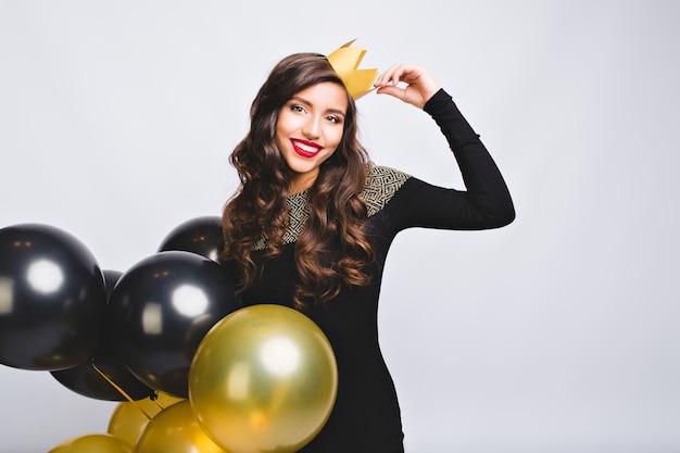 Ritratto incredibile bella donna che celebra le vacanze, che tiene palloncini oro e neri, vestito nero e corona gialla, divertirsi, festa Foto Gratuite