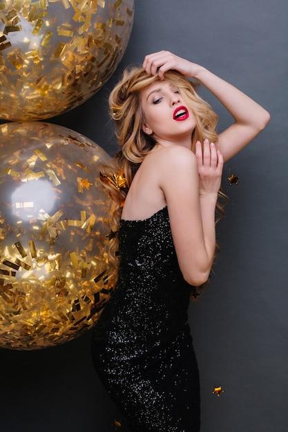 長い巻き毛のブロンドの髪、赤い唇を持つ黒い豪華なドレスの肖像画の驚くべき若い女性。お祝い、情熱、ゴージャスなモデル。 無料写真