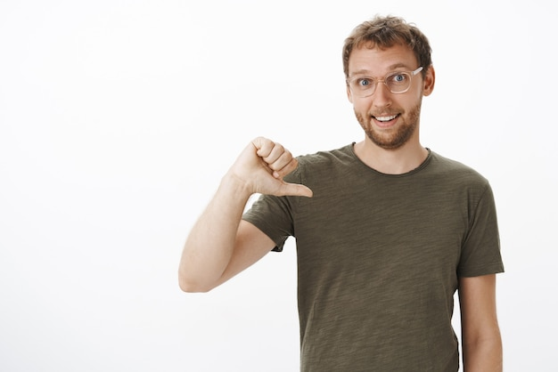 Portrait of ambitious good-looking male coworker in dark-green t-shirt pointing at himself while volunteering to be candidate smiling joyfully Free Photo