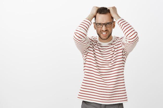 Ritratto di arrabbiato infastidito bello maschio barbuto in bicchieri, tirando i capelli fuori dalla testa e facendo smorfie dall'indignazione, in piedi sopra il muro grigio in carino pullover a strisce, essendo stressato Foto Gratuite