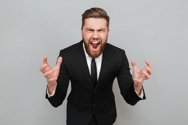 Portrait of an angry bearded man in suit shouting Free Photo