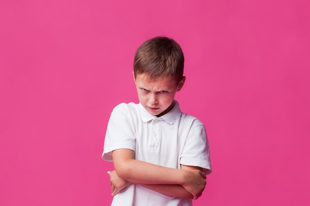 Portrait of angry boy standing over pink backdrop Free Photo