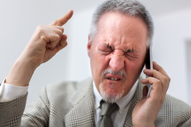 Portrait of an angry businessman yelling at phone Premium Photo
