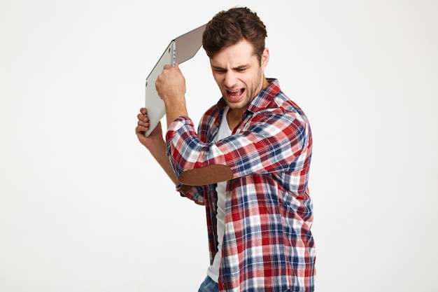 Portrait of an angry furious man throwing his laptop computer Free Photo