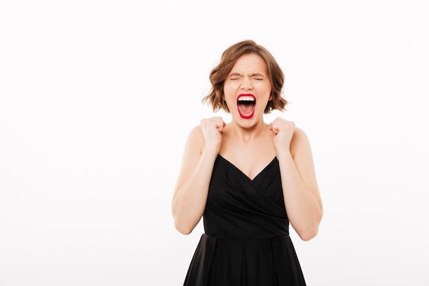 Portrait of an angry girl dressed in black dress screaming Free Photo