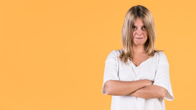 Portrait of angry woman standing on yellow background Free Photo