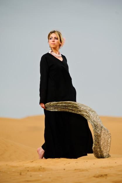 Portrait of arabic way dressed woman in yellow desert Premium Photo