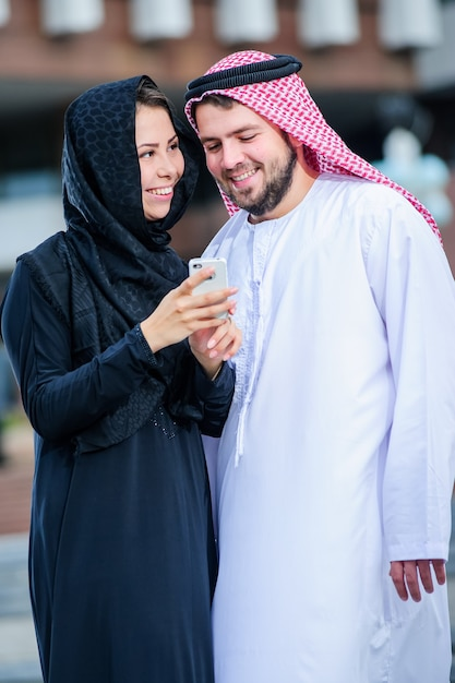 Portrait of arabic young couple play with mobile phone Premium Photo