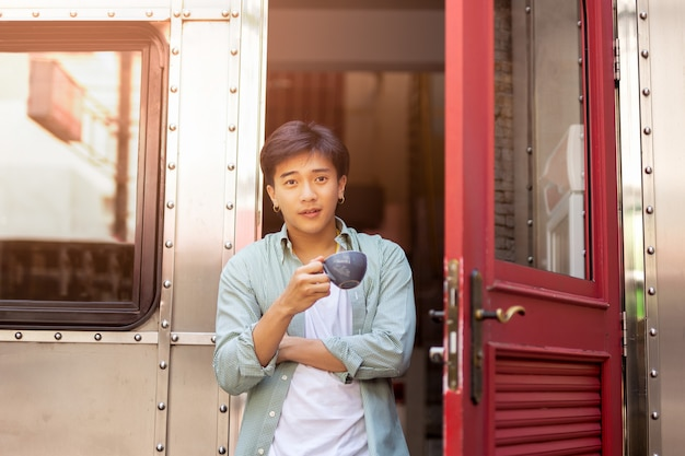 Portrait of asia man hand holding coffee cup relaxing on front door. Premium Photo