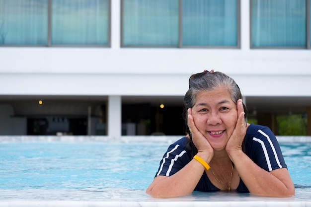 Portrait of asia mature woman standing in a swimming pool putting her chin on hand and looking forward Premium Photo