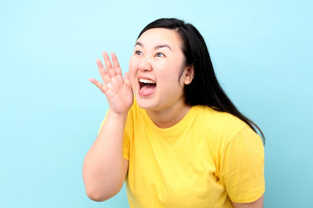Portrait asia woman yelling and hand on his mouth, isolated on blue background in studio. Premium Photo