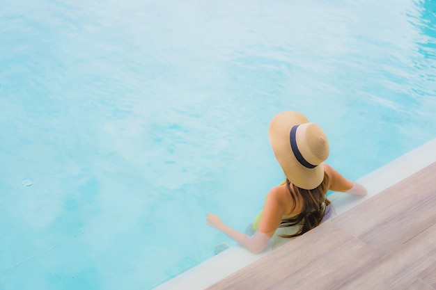 Portrait asian beautiful young woman happy smile relax around outdoor swimming pool in holiday vacation Free Photo