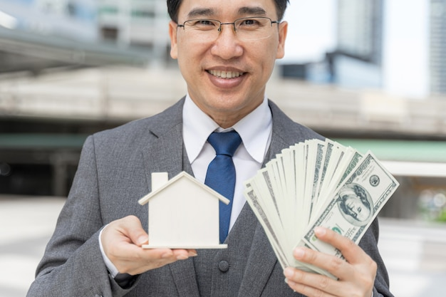 Portrait asian business man holding money us dollar bills and model house on business district Free Photo