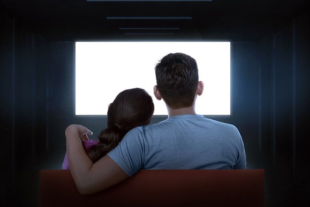 Portrait of asian couple sitting on couch watching blank tv Premium Photo
