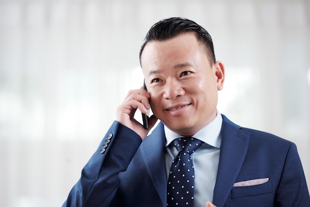 Portrait of asian entrepreneur having phone negotiation with business partner Free Photo