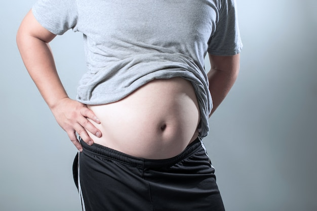 Portrait of a asian fat man show out his body and big belly. Premium Photo