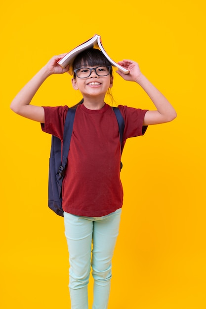 Portrait of asian funny girl kid with book on head smiling, pretty thai student in red shirt with glasses have attractive standing and looking, knowledge and wisdom Premium Photo