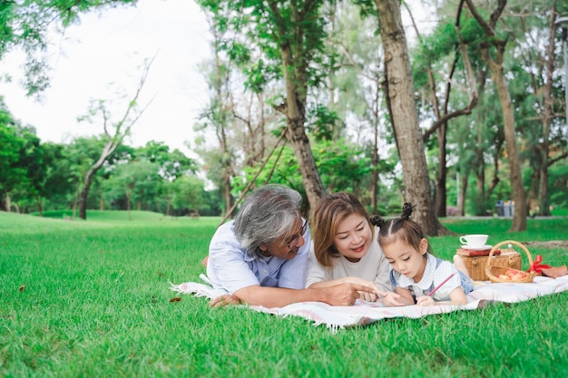 Portrait of asian grandparents and granddaughter laying on the green glass field outdoor, family enjoying picnic together in summer day concept Premium Photo