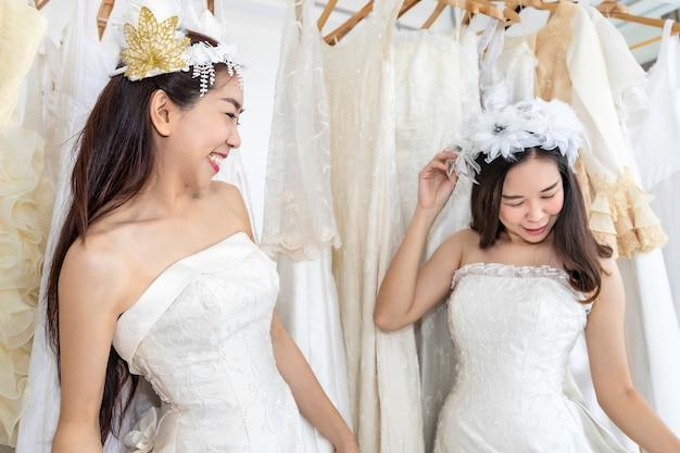 Portrait of asian homosexual couple in bride dress choosing dress in a shop.concept lgbt lesbian. Premium Photo