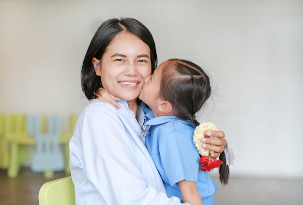 Portrait of asian little girl kissing her happy mom and hugging on mother's day in thailand. kid pay respect and give thai traditional jasmine garland to mother. Premium Photo
