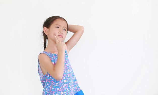 表情を考え、頬に人差し指を指す肖像画アジアの小さな子供の女の子 Premium写真