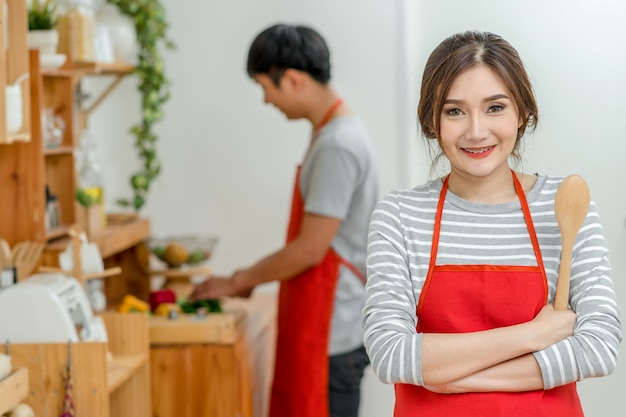 Portrait of asian lover or couple cooking with smiling action in the kitchen room Premium Photo