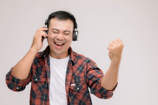 Портрет азиатского человека прослушивания песни или музыки из черных наушников. Premium Фотографии