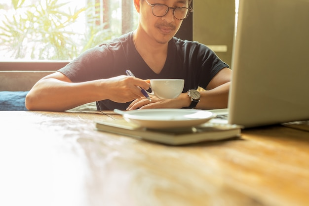 Portrait asian man with glasses having coffee break working with laptop. Premium Photo