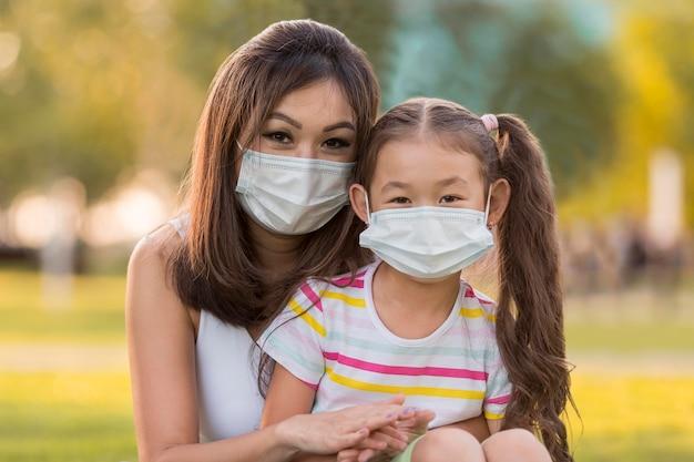 Ritratto di madre asiatica e figlia con maschere mediche Foto Gratuite