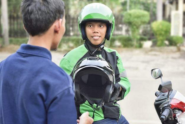 Portrait of asian motorcycle taxi driver giving the helmet Premium Photo