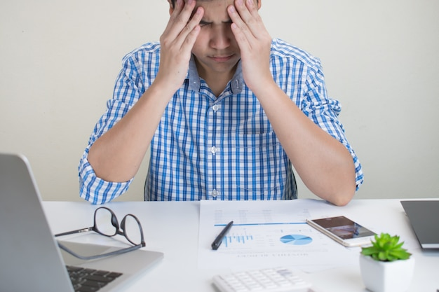 Portrait of an asian person wearing a plaid shirt, having severe headaches while working at the office. Premium Photo