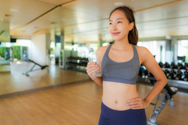 Portrait asian woman eating water in gym Free Photo