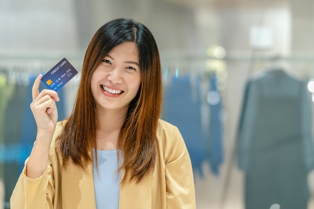 Portrait asian woman holding and presenting the credit card for online shopping in department store Premium Photo