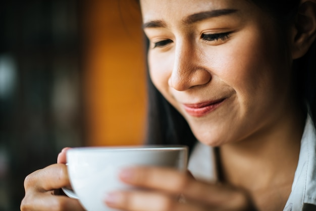 Portrait asian woman smiling relax in coffee shop cafe Free Photo