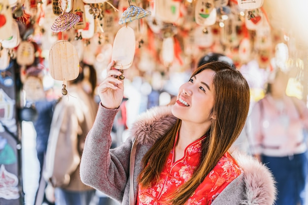 Portrait asian woman traveler looking the amulet with bell with china language in lijiang old town Premium Photo