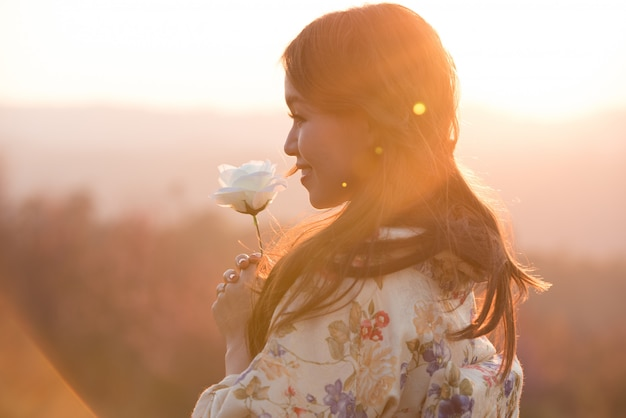 Portrait of asian woman wearing traditional japanese kimono and hands holding beautiful white rose, before sunset, love concept. Premium Photo