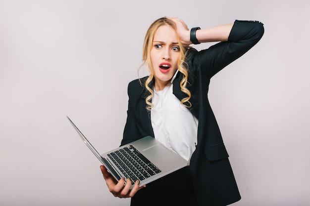 Ritratto stupito giovane donna bionda impegnata che lavora con il computer portatile. parlare al telefono, errore, umore sconvolto, essere in ritardo, impiegato, emozioni vere Foto Gratuite