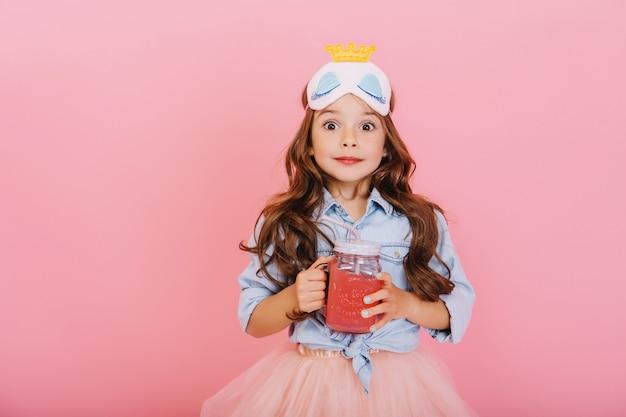 肖像画は、ピンクの背景に分離されたカメラを表現するジュースでガラスを保持しているうれしそうな小さな女の子を驚かせた。プリンセスマスクを祝って、幸せな子供時代に楽しんで面白いかわいい子供 無料写真
