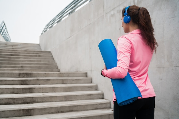 Ritratto di una donna atletica che tiene un materassino da allenamento mentre si ascolta la musica. concetto di sport e stile di vita. Foto Gratuite
