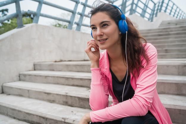 Ritratto di una donna atletica che ascolta la musica in una pausa dall'allenamento mentre è seduto sulle scale. sport e concetto di stile di vita salute. Foto Gratuite