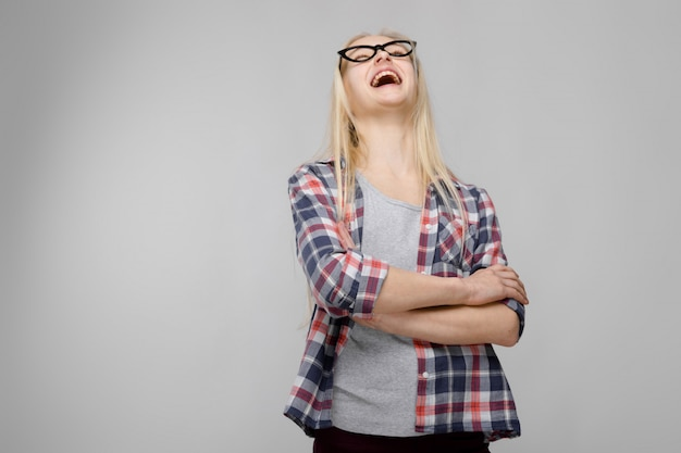 Portrait of attractive adorable blonde teenager girl in checkered clothes in glasses with arms crossed on gray Premium Photo
