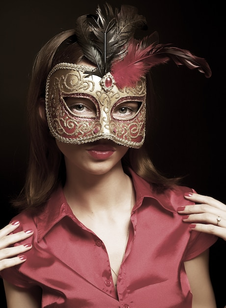 Portrait of attractive beautiful young woman wearing red cold carnival mask Premium Photo