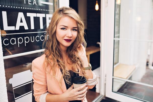 Ragazza bionda attraente del ritratto con capelli lunghi che si raffreddano sulla terrazza nella caffetteria. ha labbra vinose, tiene la tazza Foto Gratuite