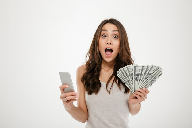 Portrait of attractive brunette female 30s winning lots of money dollar currency using her smartphone, being joyful over white Free Photo