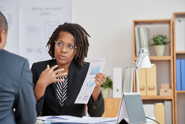 Portrait of  attractive cuban woman presenting the statistical information to her unrecognizable boss Free Photo
