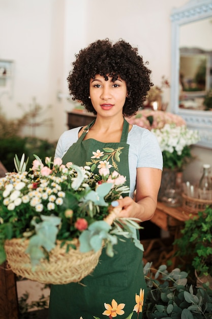 Portrait of an attractive female florist holding basket of flowers Free Photo