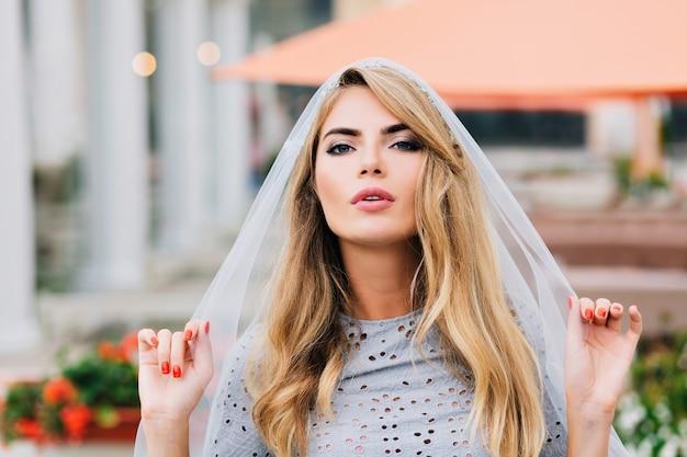 Портрет привлекательной девушки с длинными светлыми волосами на улице. она закрывает голову синей вуалью и смотрит в камеру. Бесплатные Фотографии