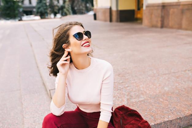 Ritratto di ragazza attraente con sorriso bianco come la neve e labbra vinose che si siedono sulle scale in città. indossa occhiali da sole e abiti vinosi. Foto Gratuite